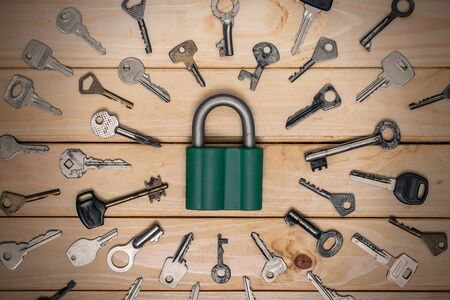 padlock surrounded by old keys on a wooden background