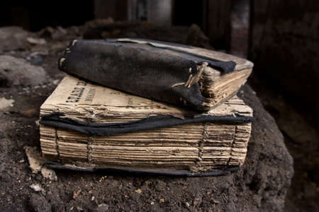 Couple of old worn prayer-books in an abandoned, gloomy, creepy room of an old building Stock Photo - 11602080