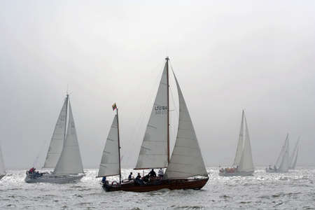 A group of yachts are racing in a regatta. Yacht silhouettes fading out in a sunny fog