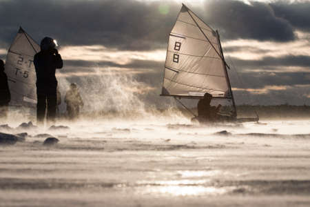 yachtsman: Junior Ice-sailor speeding up in a Race. Facing an exteme Blizzard, strong Wind