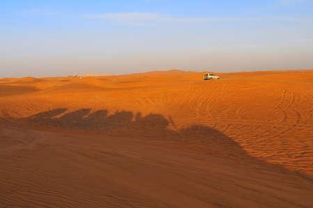 Shadows of jeeps on dune during safari near Dubai, UAE. photo