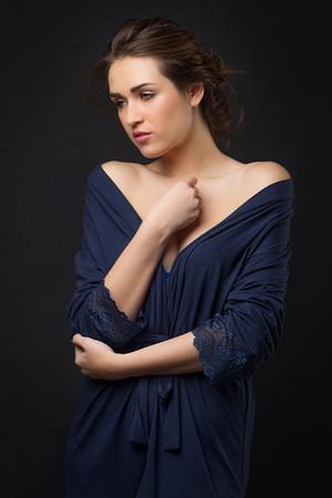 peignoir: girl in blue peignoir with bare shoulder. Dark background. Fiancee. The concept portrait in the studio.