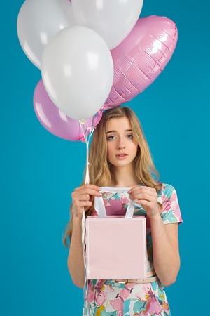 Sweet nice girl with baloons and little prersents bag in the hands on the blue background. Spring mood.