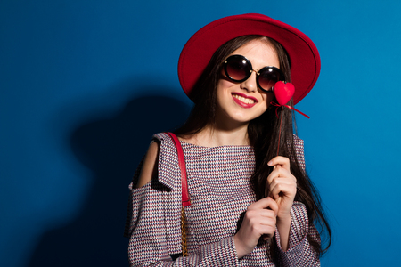Lovely model in fashionable red Hat and a red Clutch on blue background. Stock Photo