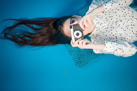 Cheerful girl lying on the floor with her camera in hands. Stock Photo