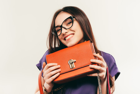 This fashionabe bag is my favorite. business woman in glasses. on a white background. Фото со стока