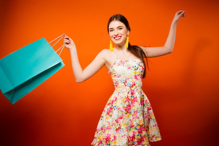 Portrait of young happy smiling woman with shopping bags. Orange background.