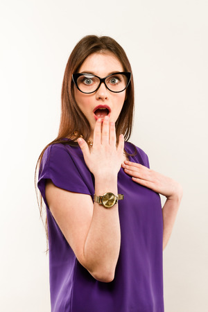 Young beautiful woman with facial expression of surprise standing over gray background. Wearing in trendy dress and glasses. Looking at the camera.