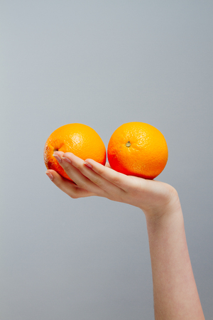 handholding: Chinese Orange on Asian woman hand on gray concrete background