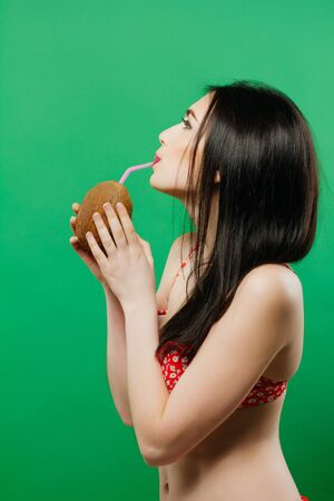 Portrait of Cute Brunette with Long Hair in Bright Swimsuit Drinking Coconut Cocktail on Green Background in Studio.