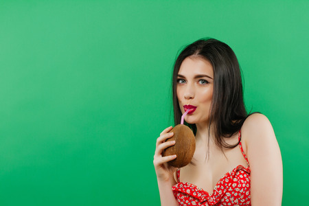 Portrait of Emotional Coquette Drinking Tropical Cocktail on Green Background in Studio.