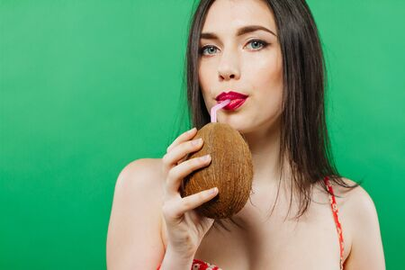 Closeup Portrait of Pretty Dark-haired Girl Drinking Cocktail in Coconut and Looking at the Camera on Green Background.