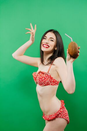 Portrait of Smiling Brunette in Bright Swimsuit with Tropical Cocktail in Hands on Green Background.