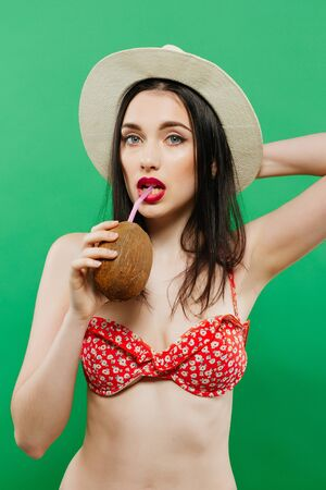 Amazing Brunette in Bright Swimwear and Cowboy Hat Posing with Cocktail in Studio on Green Background.