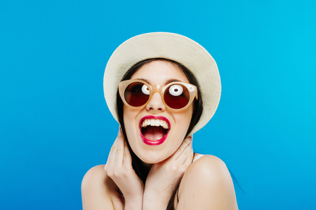 Portrait of Laughing Female Model in Fashion Sunglasses and Summer Hat on Blue Background. Stock Photo - 75947694