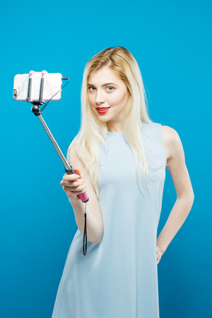 Portrait of Joyous Blonde Taking Photo Using Selfie Stick on Blue Background. Cute Girl in Dress Photographing Herself by Smartphone in Studio.