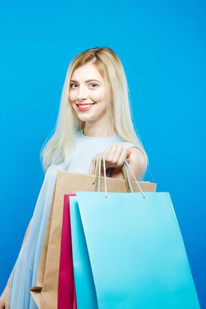 caras emociones: Pretty Woman Holding a Lot of Shopping Colorful Bags. Portrait of Cute Blonde with Long Hair on Blue Background.