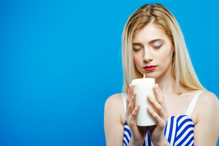 Portrait of Sad Serious Girl with Closed Eyes Holding White Candle in Her Hands. Beautiful Blonde with Bare Shoulders Wearing Striped Dress on Blue Background in Studio.