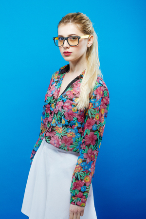 Portrait of Cute Blonde Woman with Ponytail Wearing Colorful Shirt, White Skirt and Eyeglasses on Blue Background. Sensual Girl is Posing in Studio.