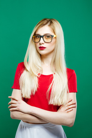 Seriuos Girl Wearing Eyeglasses, Red Top and White Skirt on Green Background. Portrait of Young Beautiful Woman with Sensual Lips and Long Hair in Studio.