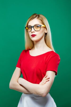 Portrait of Seriuos Girl Wearing Eyeglasses, Red Top and White Skirt on Green Background. Young Beautiful Woman with Sensual Lips and Long Hair in Studio.