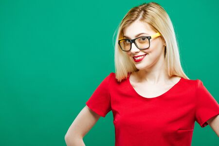 Portrait of Smiling Surprised Girl in Red Top and Eyeglasses. Sensual Pretty Blonde with Long Hair is Posing on Green Background in Studio. Stock Photo
