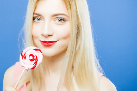 Portrait of Sensual Girl with Charming Smile and Colorful Lollipop in Hands on Blue Background in Studio.
