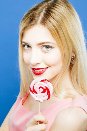 Closeup Portrait of Cute Blond-haired Girl with Colorful Lollipop in Hands on Blue Background in Studio.