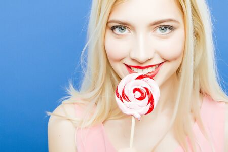 Coquettish Young Blonde with Red Sensual Lips and Long Hair is Looking at the Camera Holding Lollipop in Hand near Her Face on Blue Background in Studio.