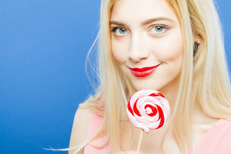Amazing Blonde with Sensual Lips and Long Hair is Looking at the Camera Holding Lollipop in Hand on Blue Background in Studio. Stock Photo