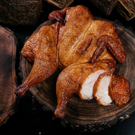 Golden, fresh, appetizing whole chicken cooked on smoke, grill, BBQ. Snacks for beer, for gourmets. Natural healthy homemade food. High quality photo