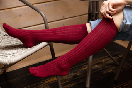 A young Model girl on a chair in violet colored socks sits on a chair and poses. Close-up. High quality photo