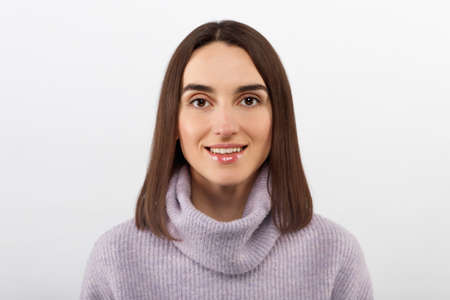 Studio shot of smiling glad woman has appealing appearance, smiles broadly, dressed purple sweater, poses against white background expresses positive emotions likes what she sees, rejoices new purchase. High quality photo Stock fotó