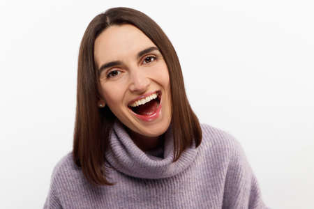 Studio shot of smiling glad woman has appealing appearance, smiles broadly, dressed purple sweater, poses against white background expresses positive emotions likes what she sees, rejoices new purchase. High quality photo