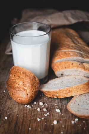 Healthy food. Long loaf of rural bread with two cut-off pieces lie on a wooden chopping board and a glass of fresh milk. Dark background 版權商用圖片