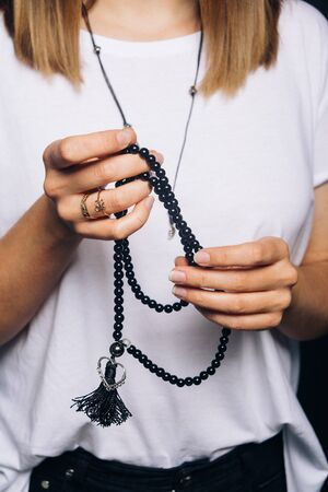 Black beads bracelet in girl hand. Can be used as fashion accessories, also as praying beads, for counting prayers or practicing mindfulness meditation. Some believe black stone has protection power 免版税图像