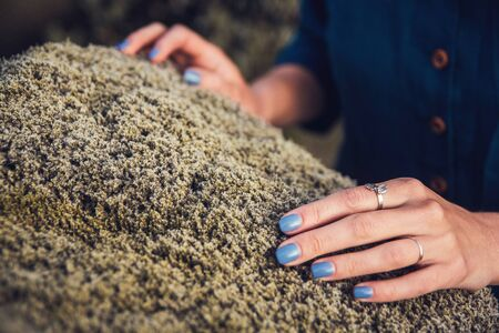 Cinematic view of thoughtfull woman in depression touching the stone moss in nature and exchanging emotion energy