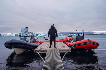 The man standing on pier in winter. Stylish winter clothes. Icebergs in Jokulsarlon lagoon