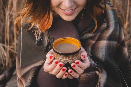 Girls hands holding a hot cup. Close-up