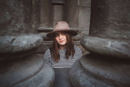 Beautiful woman in a hat and striped shirt looking at the camera. Close-up portrait Фото со стока