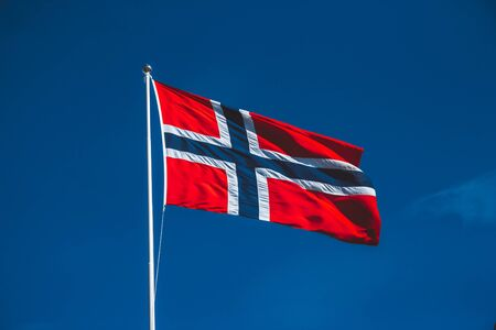 Norwegian flag against the blue sky. The wind blows against the blue sky without clouds Stok Fotoğraf