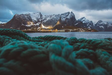 Norway rorbu houses and mountains rocks over fjord landscape scandinavian travel view Lofoten islands. Green ropes in the foreground Фото со стока