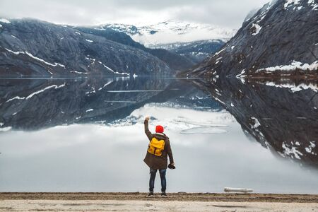 Traveler man with a yellow backpack wearing a red hat standing on the background of mountains and lake enjoying landscape. Travel lifestyle concept. Shoot from the back