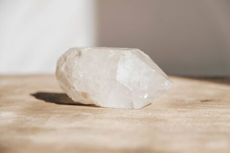 Quartz crystal on a wooden background. Copy, empty space for text.