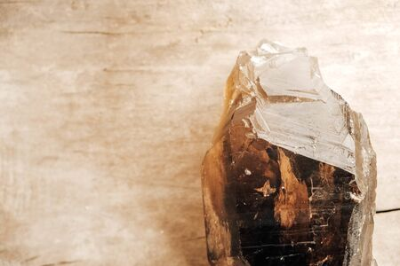 Smoky quartz crystal on a wooden background. Copy, empty space for text.