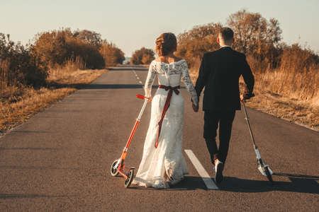 Wedding couple riding a on scooters along the road outside the city at sunset 版權商用圖片