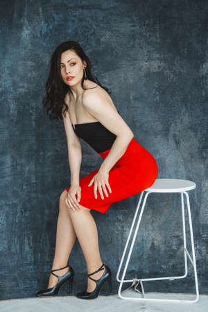 Fashion portrait of a stylish brunette girl wearing a black dress. Woman with long hair wearing red earrings. Model sitting on chair. Set on a gray background