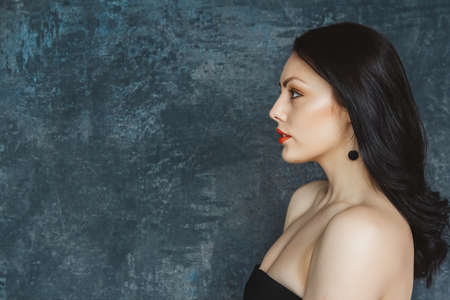 Fashionable portrait beautiful woman of a stylish brunette with red lips. Woman with long hair wearing black earrings. Set on gray background