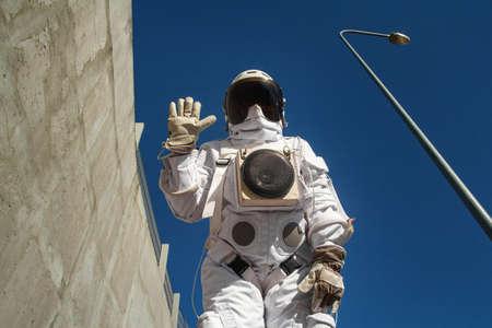 Futuristic astronaut in a helmet against gray walls. Fantastic Cosmic Costume.