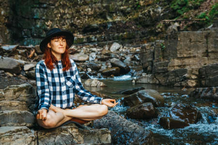 Beautiful girl with red hair in a hat and shirt meditating on rocks in a lotus position against a waterfall. Space for your text message or promotional content